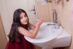 One beautiful little middle eastern arab girl with red dress is washing her hands in the bathroom. Royalty Free Stock Images