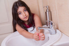 One beautiful little middle eastern arab girl with red dress is washing her hands in the bathroom. 
