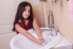 One beautiful little middle eastern arab girl with red dress is washing her hands in the bathroom. Royalty Free Stock Photo