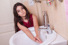 One beautiful little middle eastern arab girl with red dress is washing her hands in the bathroom. Stock Photo