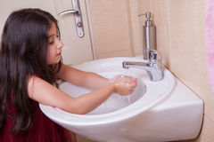One beautiful little middle eastern arab girl with red dress is washing her hands in the bathroom. Royalty Free Stock Photography