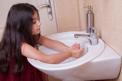 One beautiful little middle eastern arab girl with red dress is washing her hands in the bathroom. Stock Photography