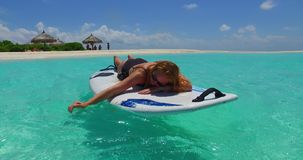 V11974 one 1 beautiful young girl in bikini sunbathing on surfboard paddleboard and relaxing by the aqua blue sea water Stock Photo