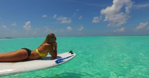 V11917 one 1 beautiful young girl in bikini sunbathing on surfboard paddleboard and relaxing by the aqua blue sea water Stock Images