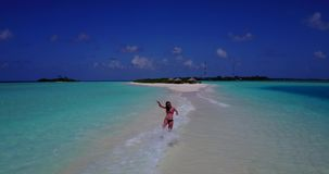 V13787 one beautiful young girl in bikini sunbathing and walking by the aqua blue sea water on white sand in the sun Stock Photos