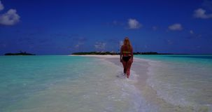 V13750 one beautiful young girl in bikini sunbathing and walking by the aqua blue sea water on white sand in the sun Stock Photos
