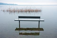 One benche in the park, by the lake,. Are submerged by water on a winter day Royalty Free Stock Photos