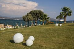 One of the best resorts on the coast of Didim, Turkey. Palm trees on the lawn of hotel territory. View of the beautiful sea, mountains, clouds Royalty Free Stock Photo