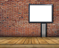One big blank billboard attached to a brick wall inside with wooden floor. Close Stock Photo