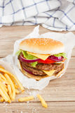One big burger with french fries Royalty Free Stock Images