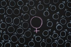 One big female gender symbol among male ones stock images