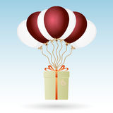 One big gift package soaring with seven helium balloons Royalty Free Stock Photo