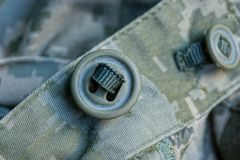 One green button on camouflage army clothes royalty free stock image