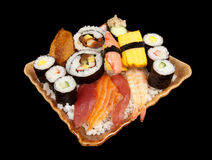 One Big Pile of Sushi. Various pieces of sushi stacked on a plate on a pile of white rice isolated on black Royalty Free Stock Photography