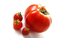 One big and three small tomatoes. Royalty Free Stock Photos