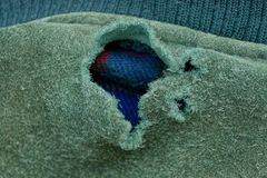 Big torn hole on the green fabric of old clothes. One big torn hole on the green fabric of old clothes stock photos