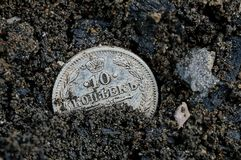 One white old silver coin lies in black earth royalty free stock images