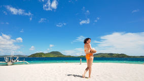 One bikini girl holds coconut on white beach Royalty Free Stock Image