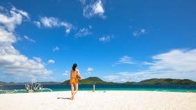 One bikini girl holds coconut on white beach Stock Image