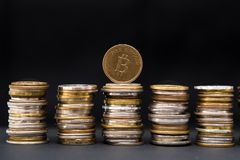 One bitcoin artificial coin on stack of mixed coins, on dark background with text space. stock photo