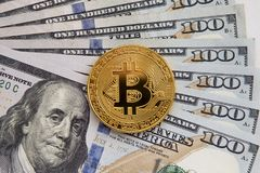 One Bitcoin on banknotes. Closeup, Macro shot. Buying bitcoins for dollars. Selling gold bitcoin. Profit from trading on the stock exchange cryptocurrencies Stock Image