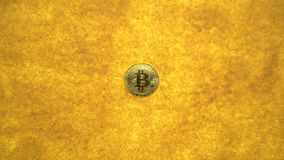Bitcoin on golden sand. One bitcoin crypto coin on a shiny golden sand background with backlight, top view. zoom effect stock video footage