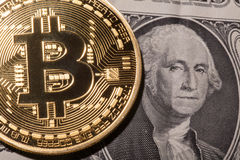 One Bitcoin on dollar banknote. Royalty Free Stock Images