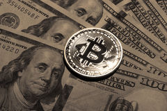 One Bitcoin on hundred dollars bills. Closeup, macro shot Stock Photo
