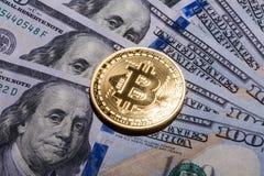 One Bitcoin on hundred dollars bills. Closeup, macro shot Stock Photography