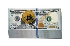 One Bitcoin on hundred dollars bills. Closeup, macro shot isolated on a white background. Earnings on the mining of cryptocurrencies. The increased rate of Royalty Free Stock Photos