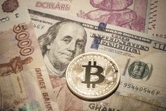 One Bitcoin on multicurrency banknotes. Closeup, Macro shot Stock Photos