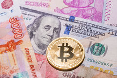One Bitcoin on multicurrency banknotes. Stock Photo