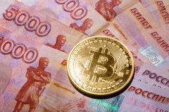 One Bitcoin on Russian rubles banknotes. Stock Photo