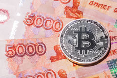 One Bitcoin on Russian rubles banknotes. Royalty Free Stock Photo