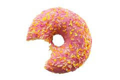 One bite missing of donut with pink frosting and colorful sugar sprinkles isolated on white background Stock Photos