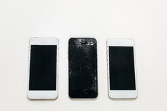 One black broken phone and two white whole next. Are on the table, two white sides black royalty free stock images