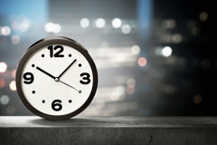 One black clock on the low wall with blurred city lights Royalty Free Stock Images