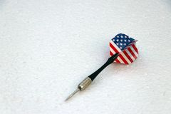 One black dart with USA flag of the wing on the white foam board royalty free stock images