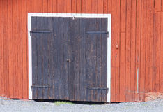 One black door in a red barn wall Royalty Free Stock Photography