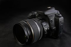 One black camera with zoom lens isolated on black background Stock Image