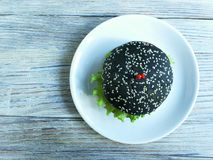 Black Burger with spaciou in the form of hearts on white wooden background. One black hamburger on a white plate on a white wooden background with fading with Stock Images
