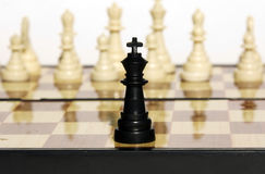 One black king against a number of white figures. The figures of chess located on a board where from black one king against the whole wax white is necessary Stock Image