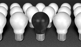 One black light bulb among many white ones on grey textured background Royalty Free Stock Photography