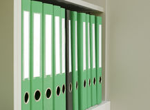 One black among the many green folder. On the shelf Royalty Free Stock Image