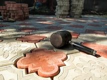 One black rubber Mallet lies on a newly laid red-and-white decorative paving slab. Work of laying a beautiful figured tile `Clover patterned` - a two colorful Stock Photography