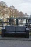 One black sofa on the street near the canal in Amsterdam. In the spring day Stock Images