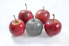 One black and white apple vs four red apples on white background Royalty Free Stock Images