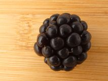 One blackberry close up on wooden plank  Royalty Free Stock Photography