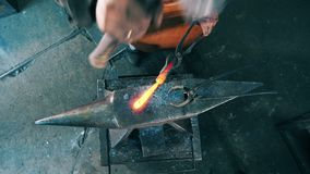 One blacksmith shapes knife on anvil, using hammer.