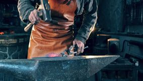 One blacksmith uses a hammer to shape a knife at a forge. 4K stock video footage